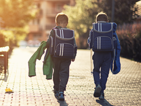 Two little boys wearing blue backpacks or schoolbags walking in residential area walkway. Little brothers are either going to school in the morning or returning from school in the evening.